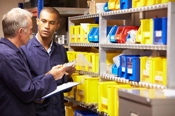 Worker And Apprentice Checking Stock Levels In Store Room