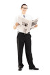 Young businessperson standing and reading a newspaper