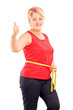 Happy woman measuring her waist after diet and giving thumb up