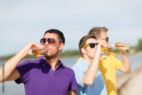 friends on the beach with bottles of drink