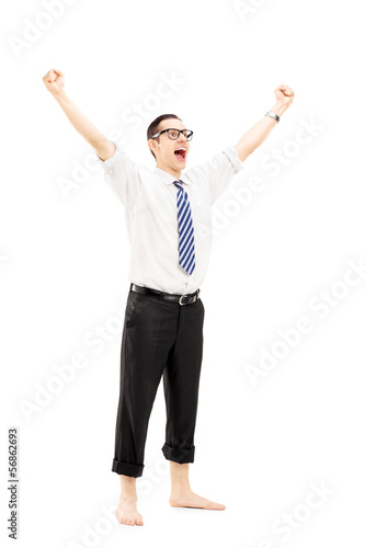 Excited barefooted guy with raised hands gesturing happiness