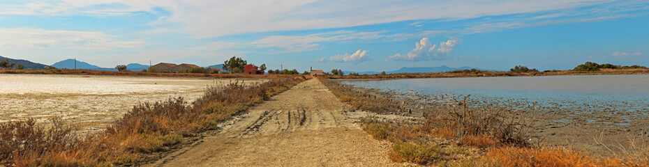 Panoramic shot of dirt road in salt flats with blue cloudy sky.