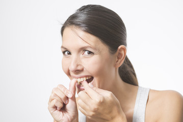 Frau benutzt Zahnseide um ihre Zähne zu pflegen