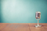 Fototapety Retro style microphone on table in front aquamarine wall