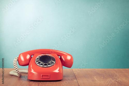 Leinwanddruck Bild Retro red telephone on wood table near aquamarine background