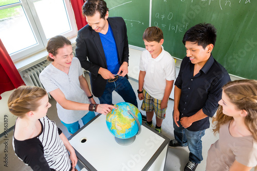 Teacher teaching students geography lessons in school