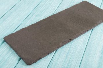 Empty Slate - Black serving platter on a blue wooden table.