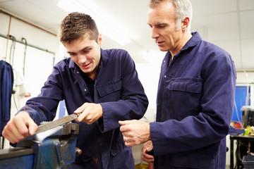Engineer Checking Trainee's Work On Factory Floor