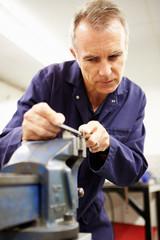 Engineer Using Metal File On Factory Floor