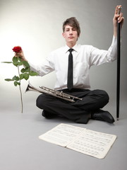 Teenage boy with trumpet, rose and notes. Love music.