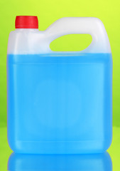 Blue liquid for car in canister on green background
