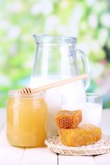 Honey and milk on wooden table on natural background
