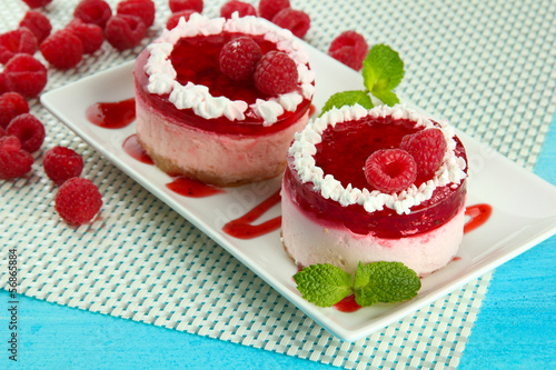 Delicious berry cakes on plate on table close-up