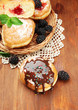 Tasty donuts with chocolate and berries on wooden table