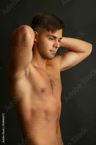 Portrait of muscle man on grey background