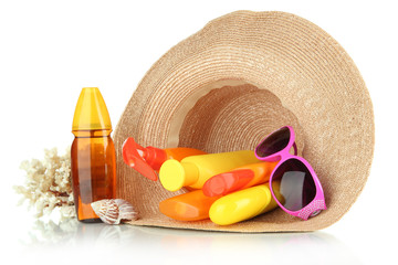 Bottles with suntan cream and sunglasses in hat isolated