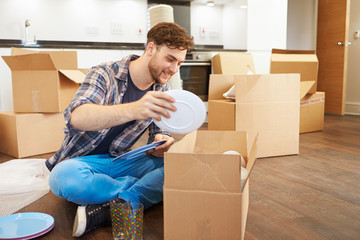 Man Moving Into New Home And Unpacking Boxes