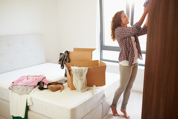 Woman Moving Into New Home And Unpacking Boxes In Bedroom