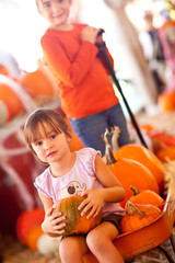 Two Young Girls Riding Wagon with Pumpkins