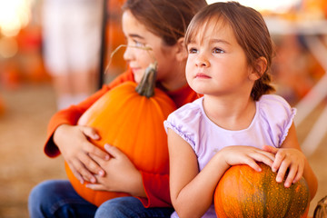 Cute Little Girls Holding Their Pumpkins At A Pumpkin Patch