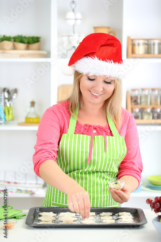Woman in kitchen during cooking Christmas biscuits
