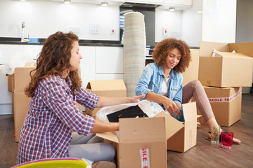 Two Women Moving Into New Home And Unpacking Boxes