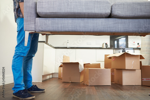 canvas print picture Close Up Of Man Carrying Sofa As He Moves Into New Home