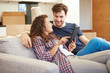 Couple Relaxing On Sofa With Digital Tablet In New Home