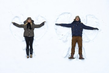 Young couple making snow angel