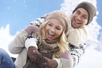 Happy loving couple sledging