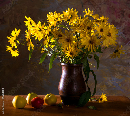 Bunch of bright yellow flowers (rudbeckia) in brown vase and app