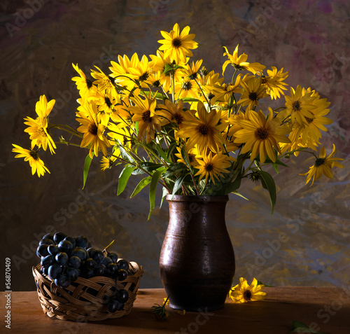 Bunch of bright yellow flowers (rudbeckia) in brown vase and gr