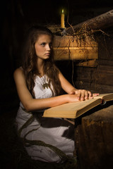 Young girl sitting with old book in a dark interior