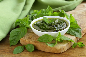 pesto sauce with basil and olive oil on a wooden table