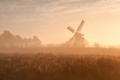 Dutch windmill in fog and morning sunshine