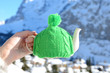 Tea pot in the knotted cap in the hand againstmountain scenery