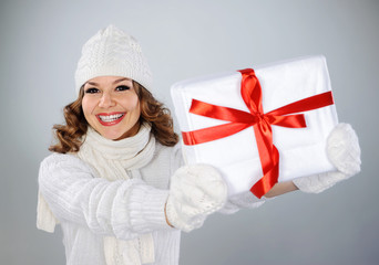 Beautiful young woman in white hat holding Christmas present