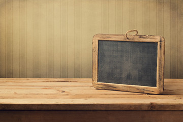 Vintage background with chalkboard on wooden table