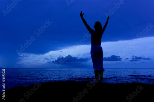 Silhouette of woman in the blue sky morning on sea beach rock