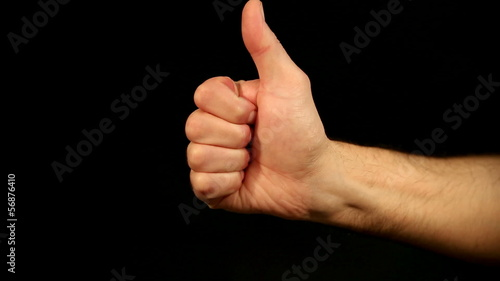 male hand lifts thumb up in front of an black background