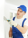 Plasterer with putty knife at wall filling poster