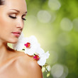 Face of  beautiful woman with a white orchid flower