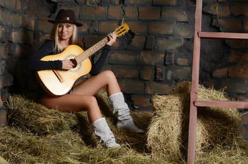 The woman with guitar on hay