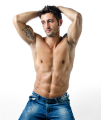Handsome and fit young man shirtless with hands behind his head
