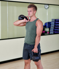 Young man exercising with kettlebells in gym