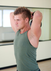 Young man exercising with kettlebell in gym