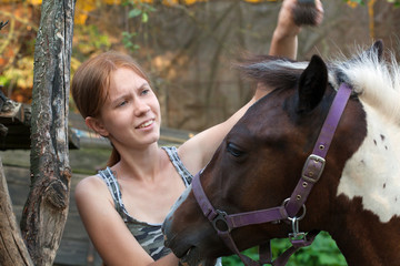 Young smiling girl grooming her horse