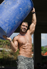 Muscular construction worker in building site holding barrel