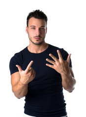 Handsome young man counting to seven with fingers and hands
