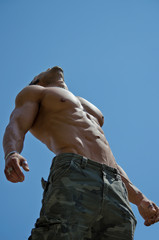 Muscular young male bodybuilder looking up in the sky